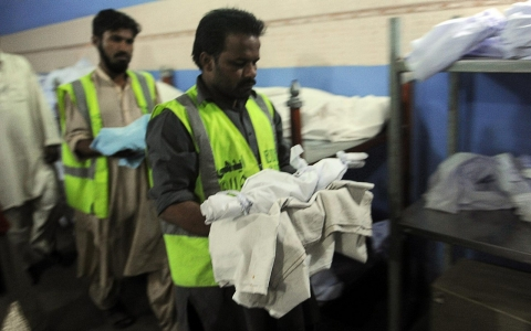 Pakistani volunteers take the corpses of two infants from the cold storage in Karachi during the burial service