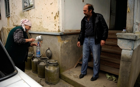 Local residents get drinking water brought to their houses in the village Akhshtyr