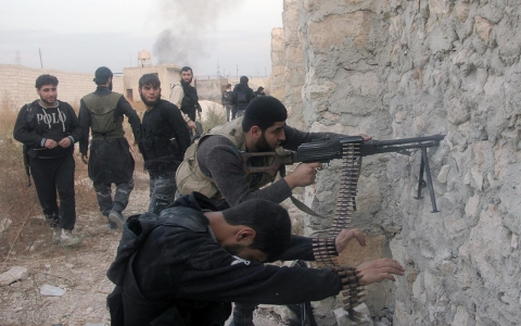 Rebel fighters in the northern city of Aleppo fire on forces loyal to the Assad regime.