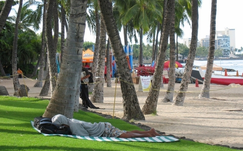 A man sleeps near a surf board rental stand at Waikiki Beach in Honolulu.