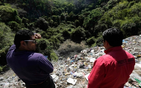 People watch at a garbage dump where remains were found outside the mountain town of Cocula, near Iguala in the southwestern state of Guerrero, November 8, 2014.