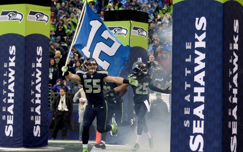"Linebacker Heath Farwell carries the ""12th Man Flag"" as the Seahawks are introduced before their playoff game against the New Orleans Saints in Seattle."