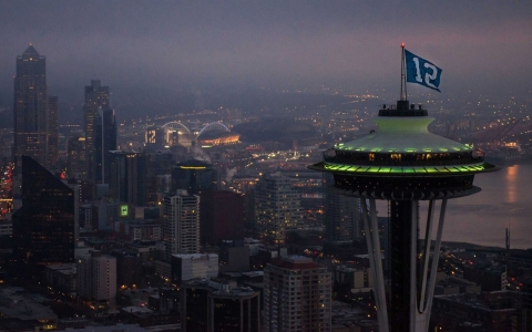 "A ""12"" flag flies above the Space Needle, while another 12 is lit in a building's windows."