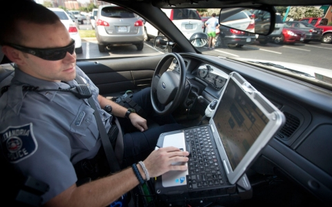 Police officer Dennis Vafier uses a laptop in his squad car to scan vehicle license plates during his patrol of the area in Alexandria, Va. on July 16, 2013.