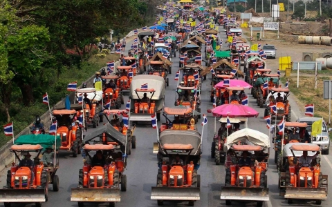 Farmers drive their tractors and other farming vehicles on a road in Ang Thong province towards Bangkok on Feb. 20, 2014.