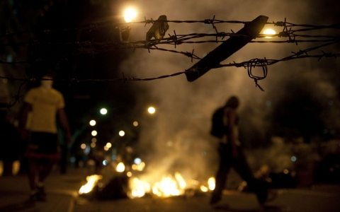 Venezuelan students light a fire during clashes with riot policemen following an anti-government protest in Caracas on Feb. 20, 2014.