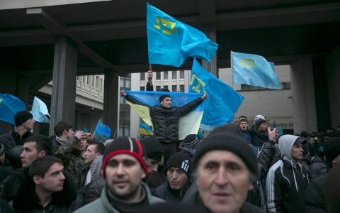 Crimean Tatars hold their flag during rallies near the Crimean parliament building in Simferopo, Ukraine on Feb. 26, 2014.