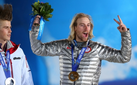 U.S. snowboarding slopestyle gold medalist Sage Kotsenburg celebrates as silver medalist Staale Sandbech of Norway looks on.
