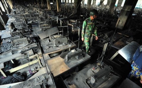 A Bangladeshi Army personnel walks through rows of burnt sewing machines after a fire in the Tazreen Fashion plant in Savar, Bangladesh, 2012.