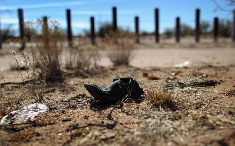 A discarded shoe lies along the porous U.S.-Mexico border fence which stretches through the Sonoran Desert.