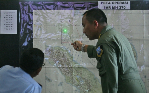 Indonesian Air Force officers examine a map of the Malacca Strait during a briefing following a search operation for the missing Malaysia Airlines Boeing 777