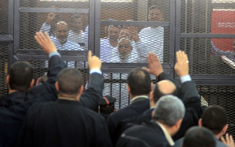 uslim Brotherhood Leader Mohamed Badie (R) and 47 other defendants stand behind bars during the trial of Brotherhood members