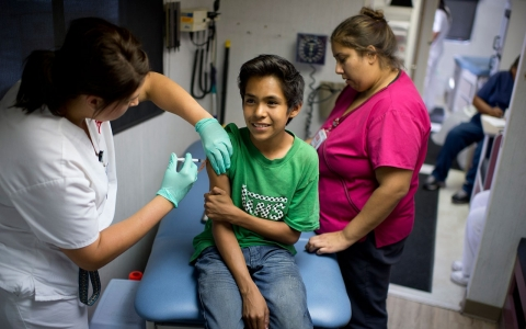Public school student Julio Valenzuela, 11, receives a Measles, Mumps and Rubella vaccination (MMR)