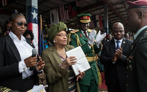 Liberian President Ellen Johnson Sirleaf presents a Bible to one of the new officers in charge of the AFL on Feb. 11, 2014.