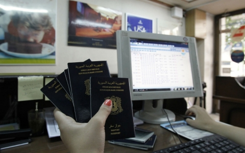A woman holding Syrian passports works on her computer in a travel agency in Damascus on September 19, 2013.