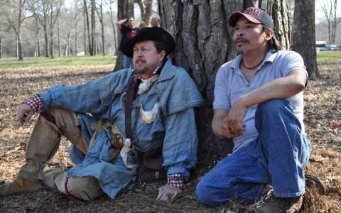 Shawn Baker, a history teacher and reenactor dressed as a Tennessee volunteer, sits with Littlehawk, a Creek reenactor from Oklahoma.