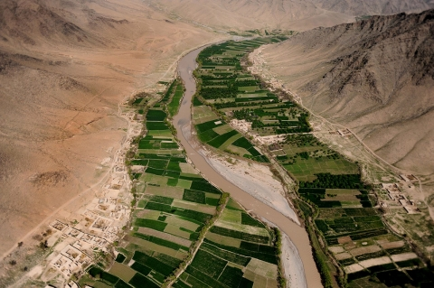 Aerial view of green farms wedged in an arid valley in southern Afghanistan's Uruzgan Province.