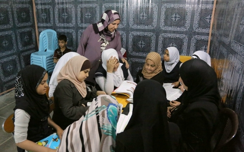 girls study at an orphanage in Baghdad, Iraq, Thursday, March 13, 2013. The director of the shelter says that she will not allow to marriage of minors at her orphanage, despite a contentious civil status draft law for Iraqi's Shiites that would permit child marriage.