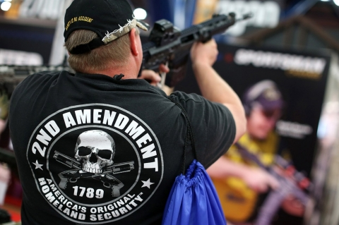 An attendee wears a 2nd amendment shirt while inspecting an assault rifle during the 2013 NRA Annual Meeting in Houston.