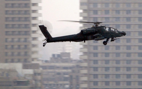 An Apache helicopter flies over Tahrir Square during a protest to support the army, in Cairo July 26, 2013.
