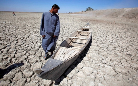 Akeed Abdullah stands next to his boat in a dried marsh in Hor al-Hammar in southern Iraq, during a drought in 2009.