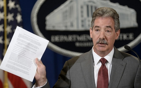 Deputy Attorney General James Cole holds up a list of guidelines during a news conference at the Justice Department in Washington, Wednesday, April 23, 2014.