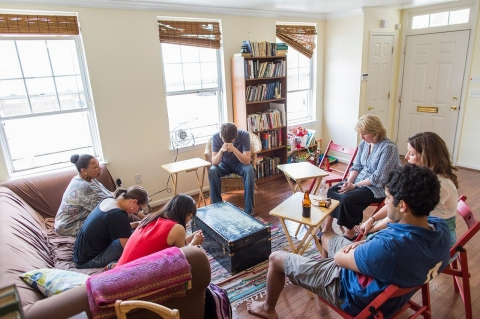 Mathew Loftus, center,  during a prayer before a meeting of New Song Community Church's mental health group in his house after Sunday service.