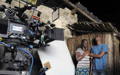 "Ivory Coast's actors Kone Abdoul Karine (R) and Bienvenue Koffi (2nd R) shoot a scene from the film ""Run."""