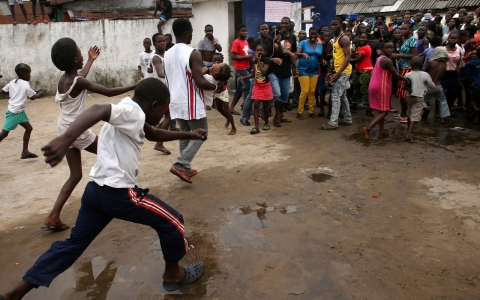A man carries out a girl from an Ebola isolation center as a mob overruns the facility in the West Point slum on August 16, 2014 in Monrovia, Liberia.