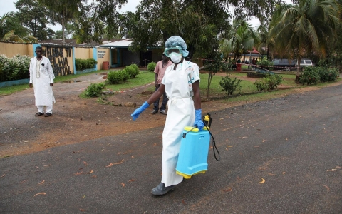A nurse from Liberia walks to spray preventives to disinfect the waiting area for visitors at the ELWA Hospital where U.S. doctor Kent Bradley was quarantined.