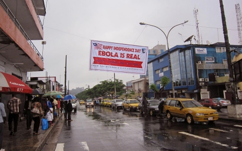people hang out in a street under a  banner which warns people to be cautious about Ebola, in Monrovia, Liberia.