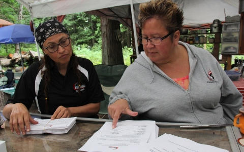 Gwaans, who also goes by her English name Beverley Clifton Percival (right), and Skayan (Anita Davis) (left) sorts through eviction notices that the Gitxsan First Nation is delivering to companies involved in resource-based industries such as logging.