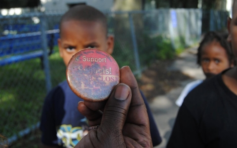 Irene Robinson holds a protest button denouncing the school closures of the 2013 school year.
