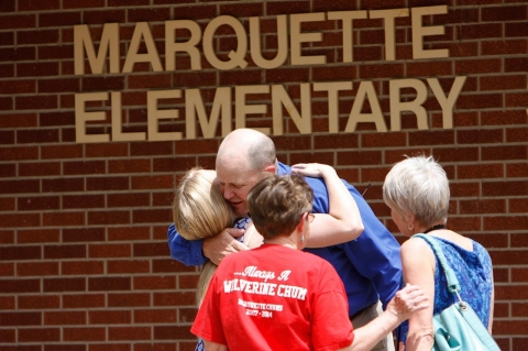 Marquette Elementary School principal Darryl Talbott hugs his daughter MaryAnne, as he stands outside the school along with his mom, Freda, and wife, Diane, on the final day of school, Tuesday, May 20, 2014, in Marquette, Kan. The school building will likely go up for sale and students will move to others schools