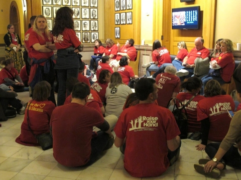 Members of the Kansas National Education Association sit outside the Kansas House chamber, following a debate on school funding legislation, Saturday, April 5, 2014, at the Statehouse in Topeka, Kan.