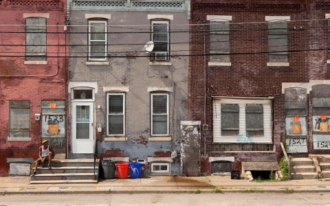 A man sits on stairs on the street in front of an abandoned home in Camden, New Jersey, U.S., on Monday, June 23, 2014.