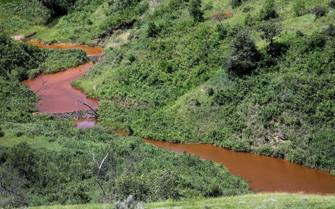 In this July 10, 2014 file photo, saltwater leaks into a stream from a massive saltwater spill from an underground pipeline on the Fort Berthold Indian Reservation near Mandaree, N.D.