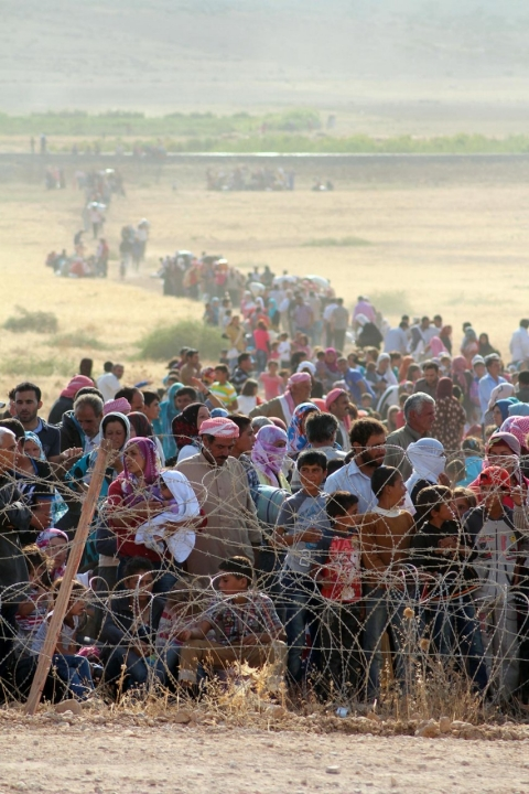 Syrians fleeing violence wait at the Turkish-Syrian border to cross into Turkey on Sept. 18, 2014 near Turkey's Sanliurfa province.