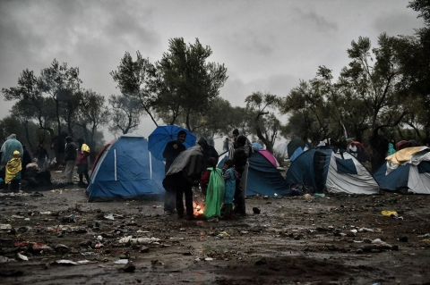 Migrants wait in heavy rain outside the Moria registration camp on Oct. 23.