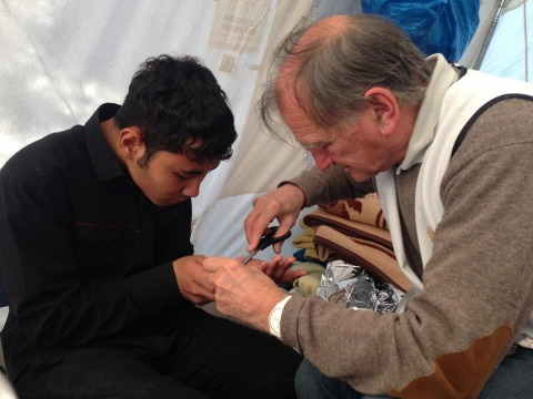 Peter Klemontschitsch, right, a retired surgeon from Holland and volunteer with the Boat Refugee Foundation, stitches a refugee's hand in a medical tent on Efthalou Beach in Lesbos.