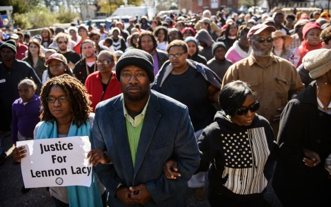 Shaune Walters, left to right, Shawn Elliott Richardson and Cassandra Ottley link arms following a march to honor the memory of Lennon Lacy on Dec. 13, 2014, in Bladenboro, N.C