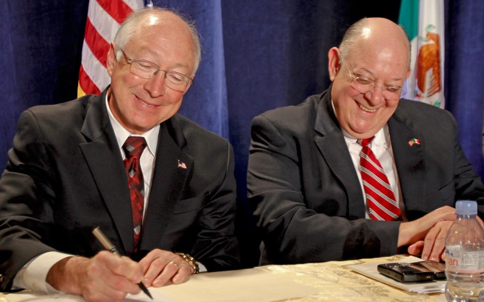U.S. Interior Secretary Ken Salazar, left, signs a document of agreement as Mexican Commissioner Roberto Salmon looks on
