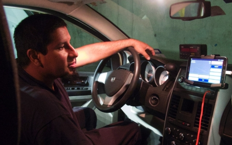 Antonio Rojas, a taxi driver in Austin, readies his dispatch system for a trip.