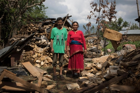 Himlal Podel and Tilkumari Podel stand in front of the rubble that was their home.
