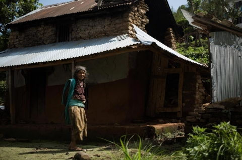 Puni Devkota stands in front of her home.
