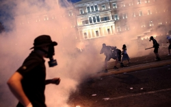 EU hails Greek austerity plan as protesters, police clash in Athens