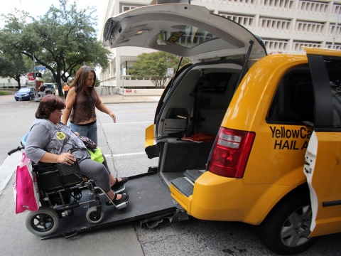 Taxi driver Crystal Gardner helps Lara Posadas board the taxi in front of City Hall after the Houston City Council's vote on Aug. 6, 2014.