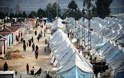 Syrian refugees walk among tents at Karkamiş refugee camp on Jan. 16, 2014 near the town of Gaziantep, Turkey.
