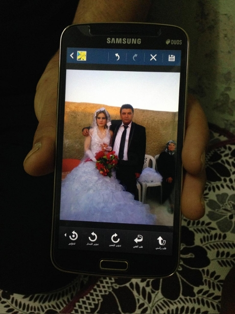 Mahmoud Ali, a Syrian refugee, shows his wedding photo. He and his wife, Iman Omar, married in Gaziantep, Turkey in 2013.