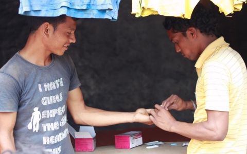 A health worker tests a young man for malaria at a mobile health clinic in Koraput, Odisha.
